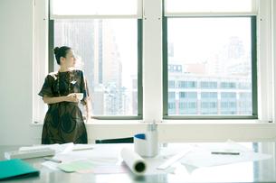 コーヒーを持ち窓際に立つ女性の写真素材 [FYI04039059]