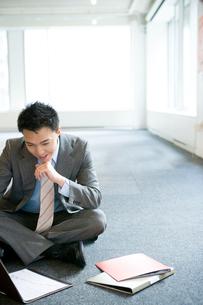 床に座り考え込む日本人ビジネス男性の写真素材 [FYI04039158]