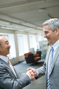 オフィスで握手するビジネスマン達の写真素材 [FYI04039180]