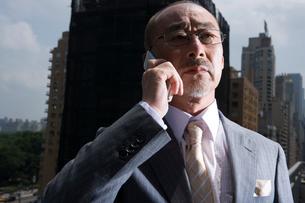 屋上で携帯で話す日本人ビジネスマンの写真素材 [FYI04039202]