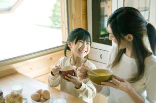 スープを飲む娘と母の写真素材 [FYI04039230]