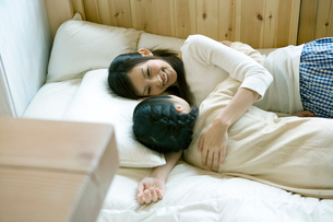 ベッドでじゃれ合う母と娘の写真素材 [FYI04039246]