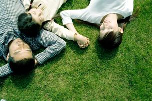 芝の上で眠る家族の写真素材 [FYI04039251]