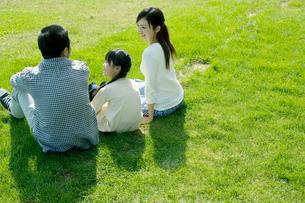 芝に座り語らう家族の写真素材 [FYI04039252]