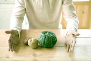 机に置かれた野菜を囲う手の写真素材 [FYI04039256]