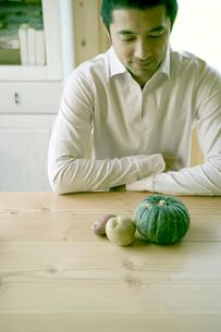 机に置かれた野菜を見つめる男性の写真素材 [FYI04039257]