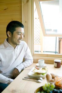 ダイニングルームで微笑む男性の写真素材 [FYI04039260]