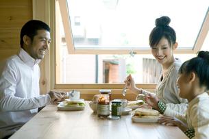 朝食を囲み笑う家族の写真素材 [FYI04039267]