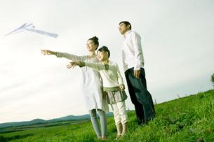 高原に立ち紙飛行機を飛ばす家族の写真素材 [FYI04039275]