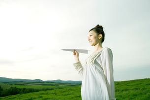 高原で紙飛行機を飛ばそうとする女性の写真素材 [FYI04039277]