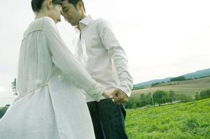 高原で頭を寄せ合う男性と女性の写真素材 [FYI04039281]