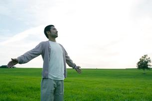 草原に立ち深呼吸をする男性の写真素材 [FYI04039292]