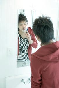 鏡を覗き髭を剃る男性の写真素材 [FYI04039308]