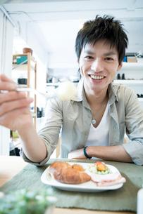 食事をしながら笑う男性の写真素材 [FYI04039341]