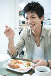 食事をしながら笑う男性の写真素材 [FYI04039343]