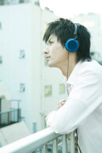 音楽を聴きながら空を見つめる男性の写真素材 [FYI04039353]