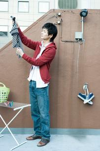 洗濯物を干す男性の写真素材 [FYI04039357]