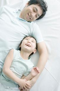 ベッドの上で笑う父と息子の写真素材 [FYI04039360]