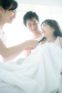 風呂上りの女の子の髪の手入れをする家族の写真素材 [FYI04039398]