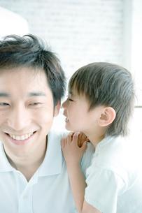 内緒話をする息子と父の写真素材 [FYI04039441]