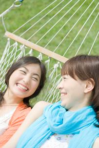 ハンモックで横になり笑う女性2人の写真素材 [FYI04039500]