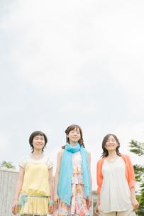 空を見つめて立つ女性3人の写真素材 [FYI04039503]