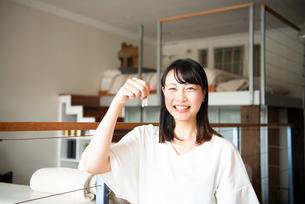 鍵を持って笑っている女性の写真素材 [FYI04039504]