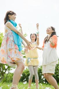 外で羽で遊ぶ女性3人の写真素材 [FYI04039512]