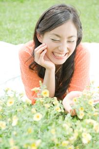 草原に寝転がり花を触る女性の写真素材 [FYI04039516]