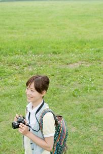 カメラを手にし草原に立つ女性の写真素材 [FYI04039526]
