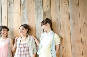壁にもたれ笑う女性3人の写真素材 [FYI04039532]