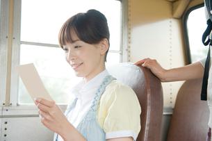 バスで手紙を読む女性の写真素材 [FYI04039537]