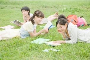 草原で勉強をする女性3人の写真素材 [FYI04039545]