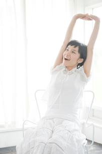 椅子に座りストレッチする女性の写真素材 [FYI04039555]