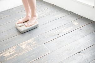 体重計に乗った女性の足下の写真素材 [FYI04039560]