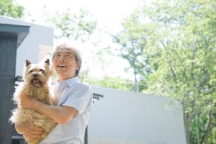 外で犬を抱く男性の写真素材 [FYI04039576]
