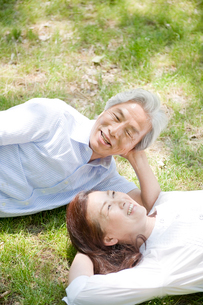 庭に寝転がる夫婦の写真素材 [FYI04039593]