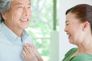 夫のボタンを留める妻の写真素材 [FYI04039609]