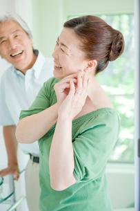 イヤリングをつける妻と笑顔の夫の写真素材 [FYI04039610]