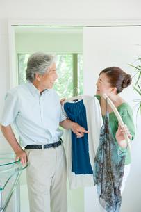 夫に服を見せる妻の写真素材 [FYI04039611]