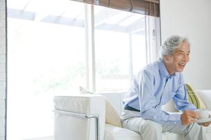 リビングでコーヒーを飲む男性の写真素材 [FYI04039615]