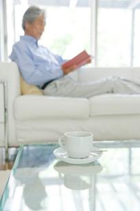 ソファで本を読む男性の写真素材 [FYI04039618]