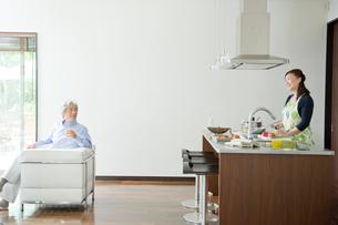 ソファに座る夫とキッチンに立つ妻の写真素材 [FYI04039636]