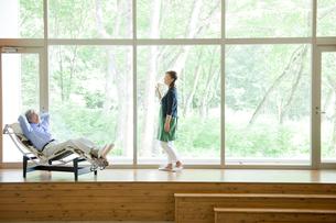 椅子に座る夫と窓際に立つ妻の写真素材 [FYI04039641]