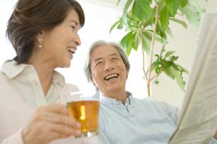 新聞を読みながら妻と一緒に笑うシニア男性の写真素材 [FYI04039663]