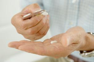薬を手に取るシニア男性の手元の写真素材 [FYI04039664]