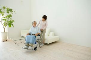 車いすに座る夫を支える妻の写真素材 [FYI04039666]