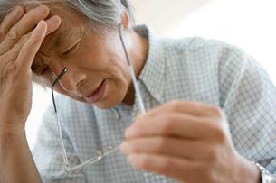 頭痛をこらえるシニア男性の写真素材 [FYI04039667]