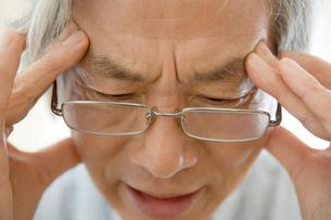 頭痛をこらえるシニア男性の写真素材 [FYI04039668]