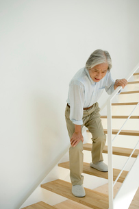 階段で膝の痛みをこらえるシニア男性の写真素材 [FYI04039669]
